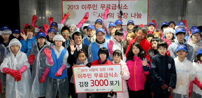 Members of Citibank Korea's service corps pose with multicultural families after making kimchi for foreign workers and their families at Global Sarang, an NGO for immigrant workers, in Seoul on Saturday. (Citibank Korea)