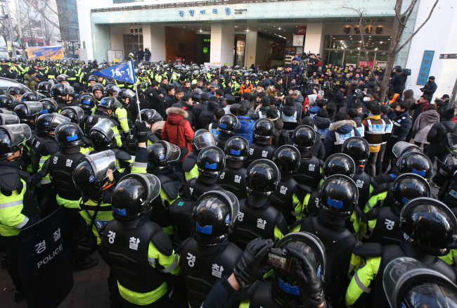 Police officers prepare to storm into a union office on Sunday. (Yonhap News)