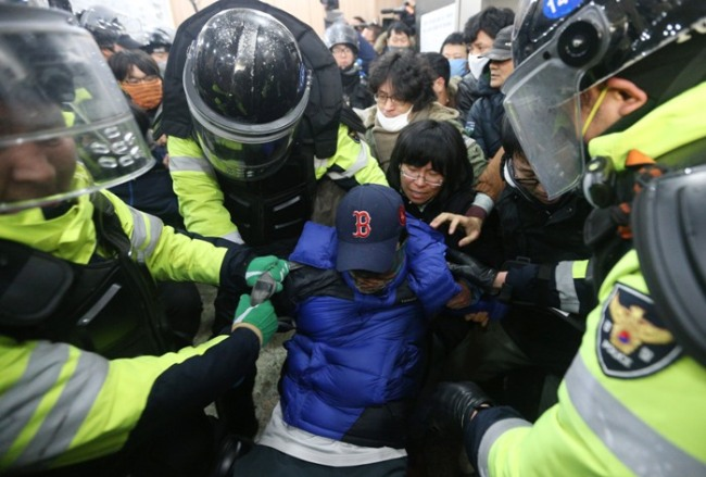 A strking railway worker is being dragged by police officers in Seoul on Sunday. (Yonhap News)