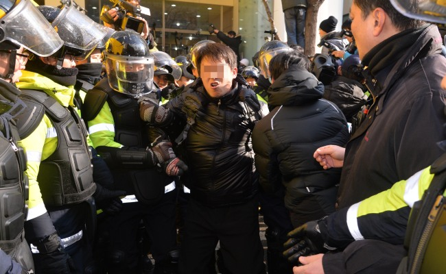 The police escort a unionist from the Korean Confederation of Trade Unions' headquarters in Seoul on Sunday.(Lee Sang-sub/The Korea Herald)