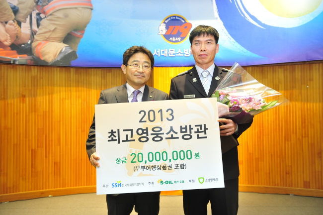 """S-Oilsenior vice president Lee Chang-jai (left) poses with the winner of the """"hero firefighter"""" of 2014 award Moon Gwon-ju from Gwangsan Fire Station in Gwangju after handing over a plaque of appreciation and a prize of 20 million won ($19.000). Moon rescued six people buried under a collapsed new building in the city in June. (S-Oil)"""