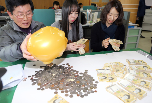 Employees of the Nosong-dong Community Center in Jeonju, North Jeolla Province, count money donated by an unidentified person in the center on Monday. (Yonhap News)