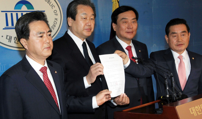 Ruling Saenuri Party and main opposition Democratic Party lawmakers hold up their agreement to set up a subcommittee for railway development plans at the National Assembly on Monday. From left: Saenuri Reps. Kim Tae-heum and Kim Moo-sung, and DP Reps. Park Ki-choon and Lee Yoon-seok. (Park Hyun-koo/The Korea Herald)