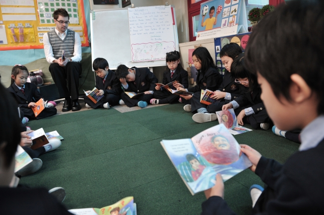 Children read English books with their teacher at a private school in Seoul. (The Korea Herald file photo)