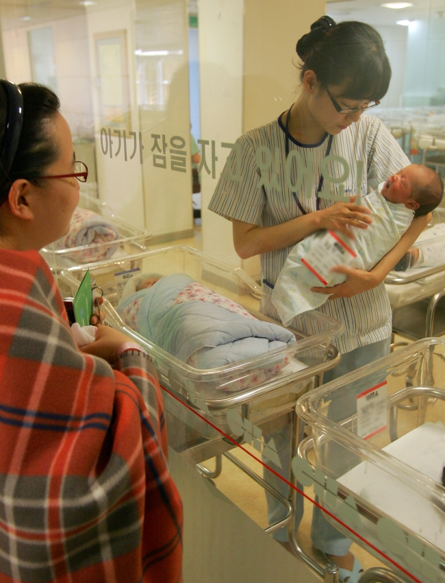 A mother (left) looks at a newborn at a hospital in Seoul. Many young mothers in Korea choose to go to postpartum centers right after they are discharged from hospitals. (The Korea Herald file)
