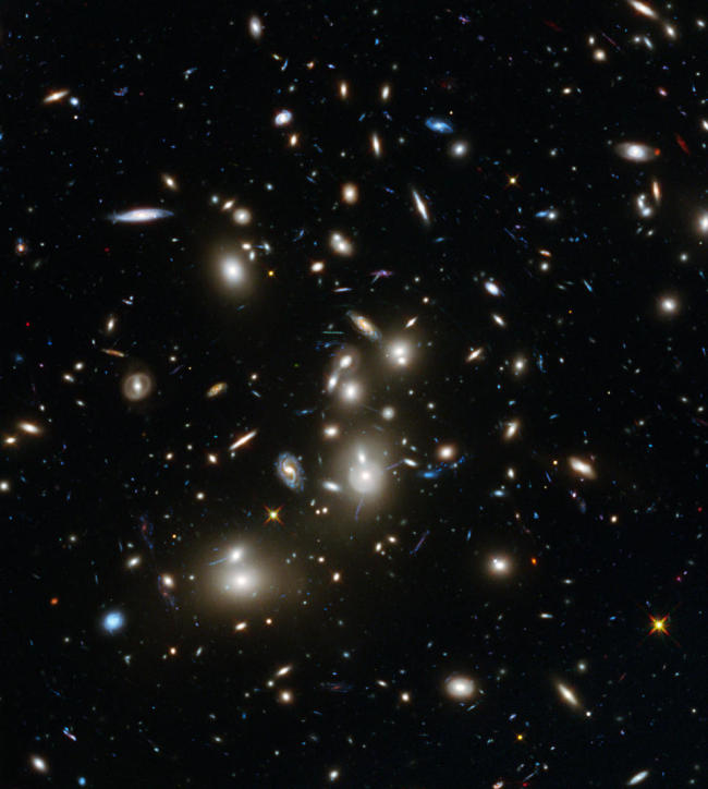 This undated image shows galaxies in the Abell 2744 cluster, and blue galaxies behind it, distorted and amplified by gravitational lensing. (AP)