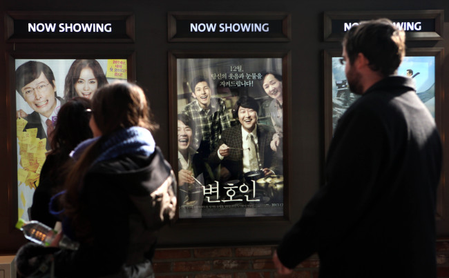 "Moviegoers look at the poster of ""The Attorney"" at a movie theater in Mapo, Seoul, Sunday. The film, based on an actual court case handled by former President Roh Moo-hyun when he was a lawyer in the 1980s, attracted more than 9 million viewers within 25 days of its release. (Yonhap News)"