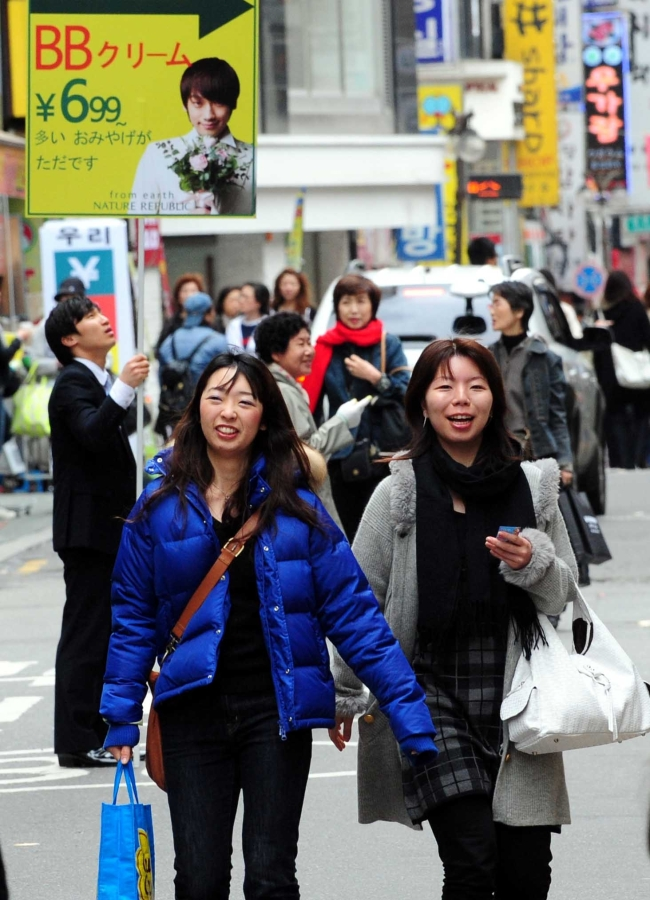 Japanese tourists walk past the Myeong-dong shopping mall in Seoul. (The Korea Herald)