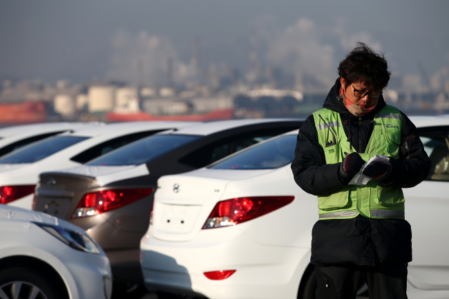 A worker takes notes as he inspects Hyundai Motor Co. vehicles bound for export at a port near the company's plant in Ulsan, on Thursday. (Bloomberg)