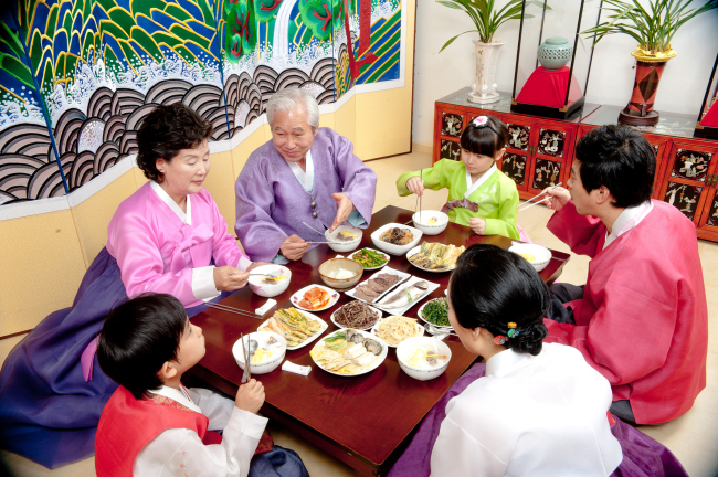 A family gathers around a traditional breakfast table laden with special dishes to celebrate the Lunar New Year, including tteokguk. (Korea Tourism Organization)