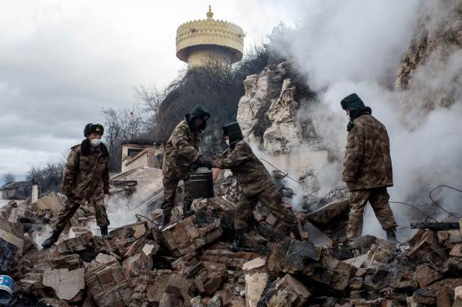 This picture taken on Jan. 12 shows rescuers sifting through the wreckage of damaged houses in the ancient Tibetan town of Gyalthang, in Shangri-La, Yunnan province, China, after a fire flattened two-thirds of the town's old center.(AFP-Yonhap)