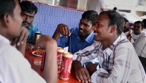 (Clockwise from left) Workers Murugan Ponnusamy, 30; Mani Munusamy, 26; Velu Arumugam, 31; and Kuberan Mani, 25, having a beer last Sunday at Spice Box restaurant at about 4 p.m. The three brothers and their uncle, Mr. Munusamy, still meet every Sunday but do so in the afternoons instead of at night. (The Straits Times)