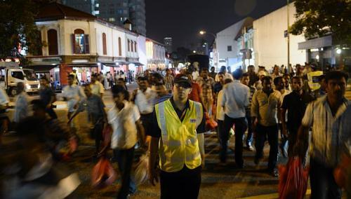 An auxiliary police officer helps to direct pedestrians in front of the busy junction at Kerbau Road in Little India on Sunday. The authorities are expected to continue to keep a close watch on the area. The stepped up patrols by auxiliary police officers are one sign of that. (The Straits Times)