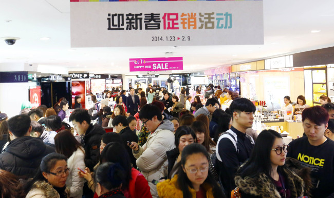 Foreign tourists shop at a duty-free store in Seoul. (Yonhap)