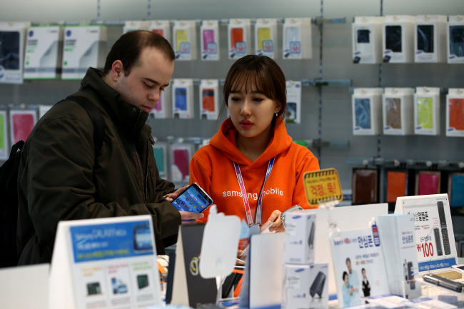 An employee helps a customer inspecting a mobile device at a Samsung Electronics Co. mobile store in Seoul. (Bloomberg)