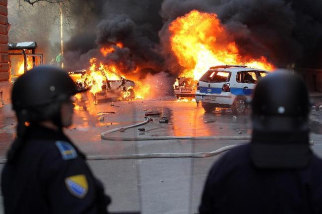 Bosnian policemen try to hold off protesters in Sarajevo on Friday. (AFP)