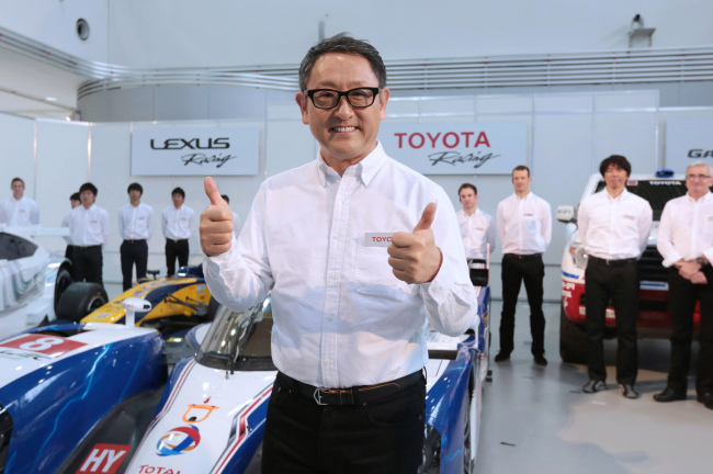 Akio Toyoda, president of Toyota Motor Corp., flashes a thumbs-up as he poses in front of drivers and members of Toyota Motorsport GmbH during a news conference on the company's motorsports activities for 2014 in Tokyo. (Bloomberg)