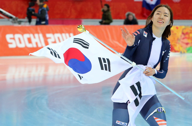 Lee Sang-hwa waves the national flag after winning the women's 500-meter speedskating race at the Adler Arena Skating Center during the 2014 Winter Olympics in Sochi, Russia, Tuesday. (Yonhap)