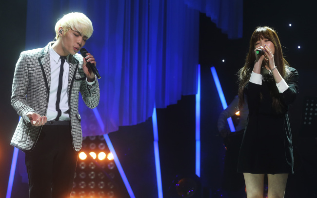 "Jonghyun (left) of SHINee and Taeyeon of SNSD sing ""Breath"" during the ""SM The Ballad Vol. 2 Joint Recital"" at the COEX Artium concert hall on Wednesday. (Yonhap)"
