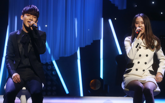 "EXO's Chen (left) and f(x)'s Krystal sing ""The Good and Bad"" during the ""SM The Ballad Vol. 2 Joint Recital"" at the COEX Artium concert hall on Wednesday. (Yonhap)"
