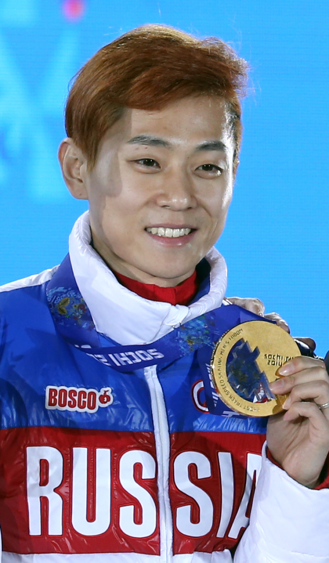 Korean-born Viktor Ahn of Russia holds out the gold medal after winning the 1,000m short track speed skating in Sochi on Saturday. (Yonhap)