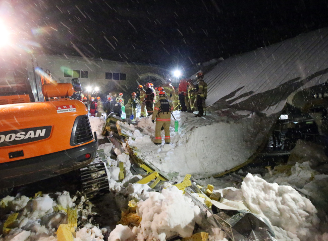 Firefighters carry out the restoration plan amid remnants of the collapsed building of a mountain resort in Gyeongju, North Gyeongsang Province, late Monday.