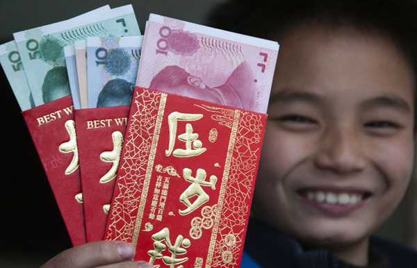 A boy shows the red envelopes he received during Spring Festival this year in Shaoyang, Hunan province. (China Daily)
