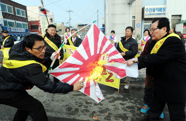 "Protestors set a Japanese rising sun flag alight during a protest over the disputed Dokdo Islets in Gangneung City, Gangwon Province, on Feb. 21. Foreign embassies unintentionally stepped into the controversy and became targets of criticism here by using country domains of Google Maps with the place names ""Liancourt Rocks"" and ""Sea of Japan."" (Yonhap)"