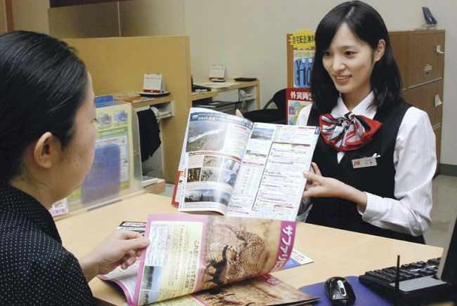A JTB Corp. employee shows a customer a brochure for unusual destinations, such as Africa and Latin America, at the travel agency's Shimbashi branch in Minato ward, Tokyo. (The Japan News)