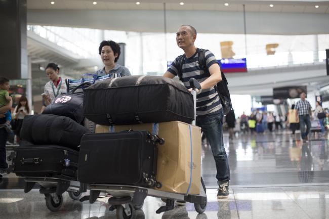 Travelers push their luggage through Hong Kong International Airport in Hong Kong. (Bloomberg)