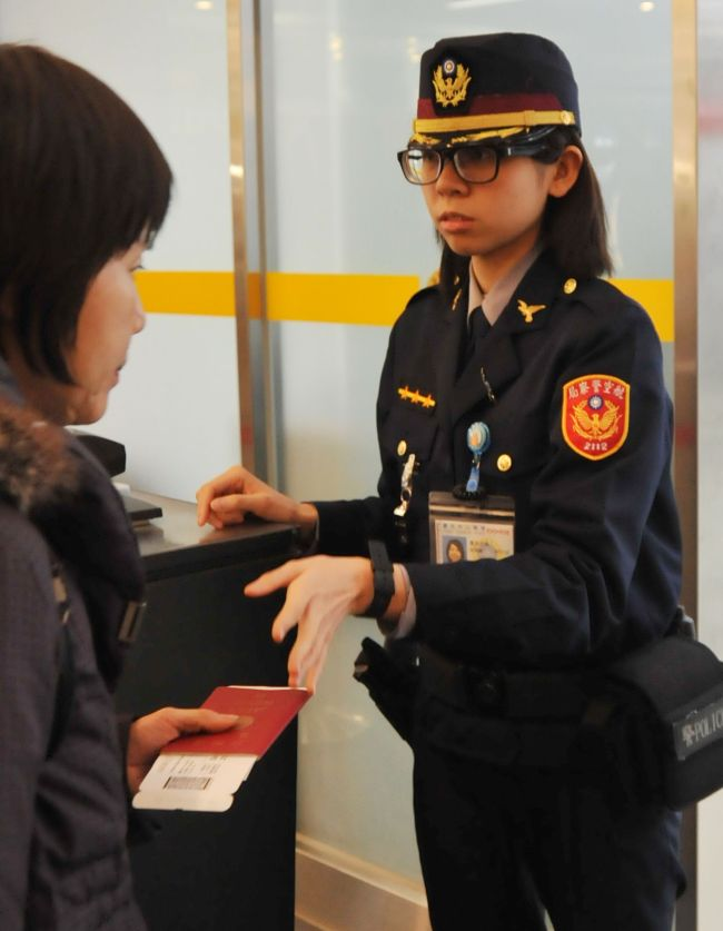 An airport security officer checks a passenger's passport and boarding pass at the Taipei Songshan Airport on Monday. (AFP-Yonhap)