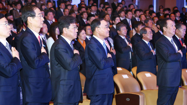 Prime Minister Chung Hong-won (fourth from left) and other government officials and business leaders pledge allegiance to the Korean flag during an event to celebrate the country's trade and commerce in Seoul on Wednesday. (Yonhap)