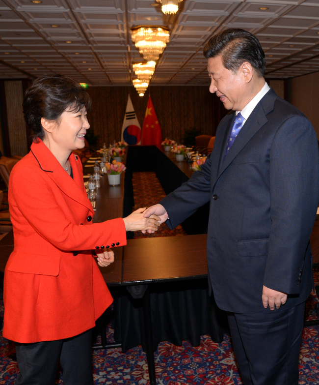 President Park Geun-hye shakes hands with Chinese President Xi Jinping in The Hague on Sunday. (Yonhap)