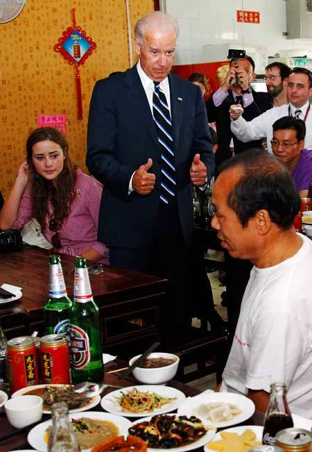 U.S. Vice President Joe Biden (center) gives a thumbs-up during lunch at Yao's Chaogan'er Restaurant in Beijing in August 2011. (AFP)