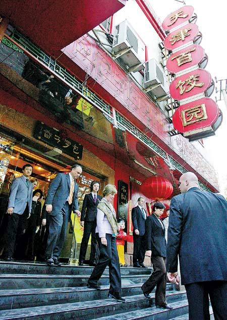 Former U.S. first lady Laura Bush (center) walks out of the Tianjin Baijiaoyuan restaurant, where she ate lunch in Beijing in November 2005. (China Daily)