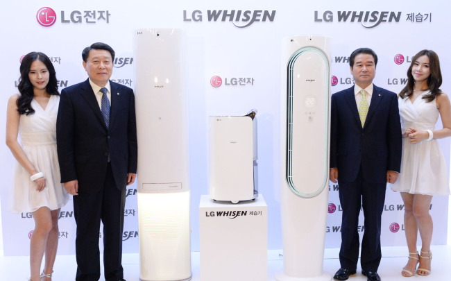 Nho Hwan-yong (second from left), president of LG Electronics' Air Conditioning & Energy Solution Company, poses with the new Whisen air conditioner and dehumidifier at a press event in Seoul on Tuesday. (LG Electronics)