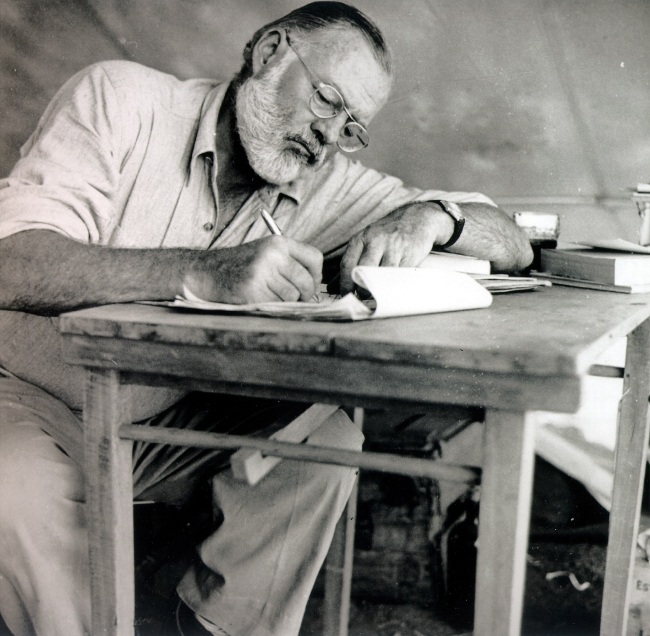 Ernest Hemingway writing at a desk while on safari in 1953. (MCT)
