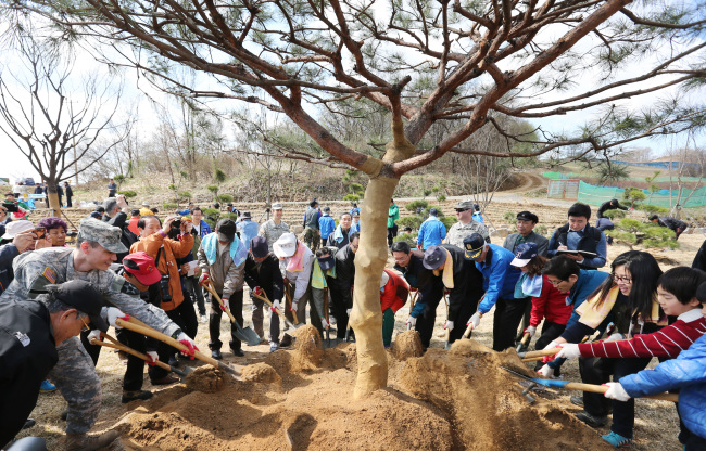Officials, citizens and U.S. soldiers plant a tree in an event to create a community forest in Paju, Gyeonggi Province, Friday, one day before Arbor Day. (Yonhap)