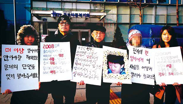 Shannon Heit (right), a Korean-American adoptee, holds rally with other adoptees in front of an adoption agency in Seoul which arranged the adoption of a 3-year-old boy beaten to death by his adoptive father in February in the U.S