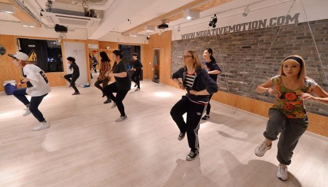 Kim Ra-young (left) teaches a K-pop dance class at Negative Motion Dance Studio. (Lee Sang-sub/ The Korea Herald)