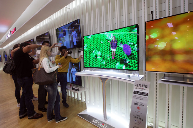 Customers take pictures of an LG Electronics curved OLED television in Seoul. ( Bloomberg)