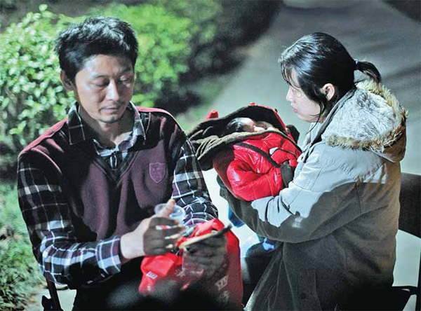 This couple from Guangzhou came to the hatch intending to give up their baby daughter, but later abandoned the idea. (China Daily)
