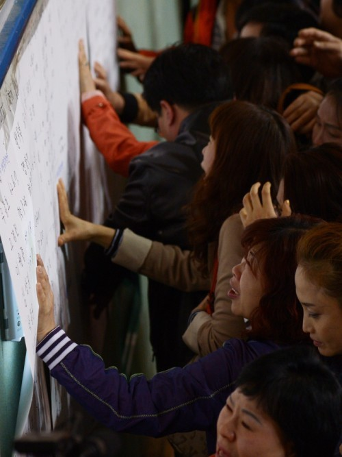 Family members of the passengers of the sunken Sewol look at the lists of passengers and survivors outside a gymnasium in Jindo, South Jeolla Province, Thursday. (The Korea Herald)