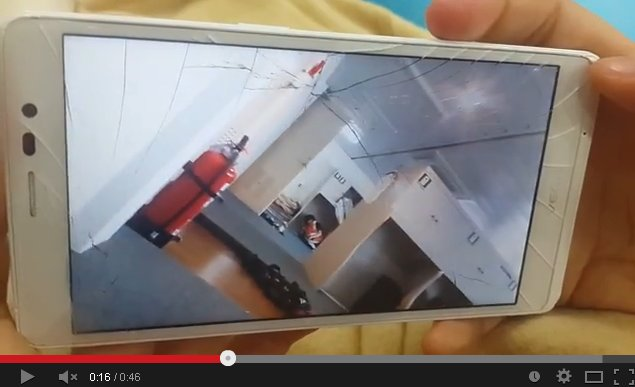 A cracked smartphone screen playing footage shows the sinking process of the Sewol. (photo: Youtube)