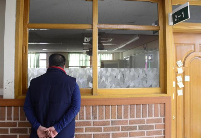 A parent of a missing child looks at a vacant classroom in Danwon High School in Ansan, on Friday. (Park Hae-mook/The Korea Herald)