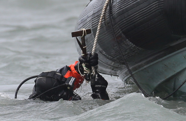 A diver carrying a hammer enters the water to search for missing passengers of the sunken Sewol off the coast of Jindo Island, South Jeolla Province, Tuesday. (Yonhap)