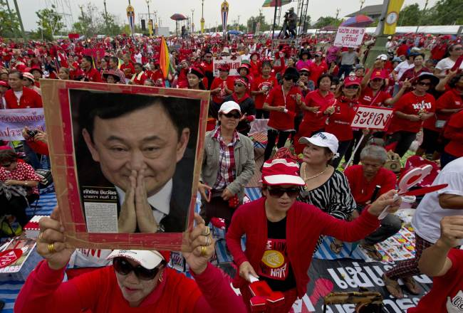 """A Thai pro-government """"Red Shirts"""" protester holds a portrait of fugitive former Prime Minister Thaksin Shinawatra during a rally in the Phutthamonthon suburb of Bangkok on April 5. (AFP-Yonhap)"""