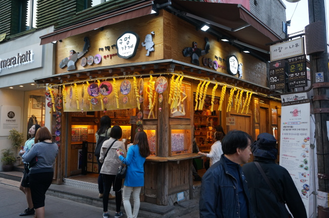 A ttakji (round comic card) gallery in Insa-dong, Seoul, hangs ice cream in cane-shaped corn puffs from its eaves. ( Lee Woo-young/The Korea Herald)