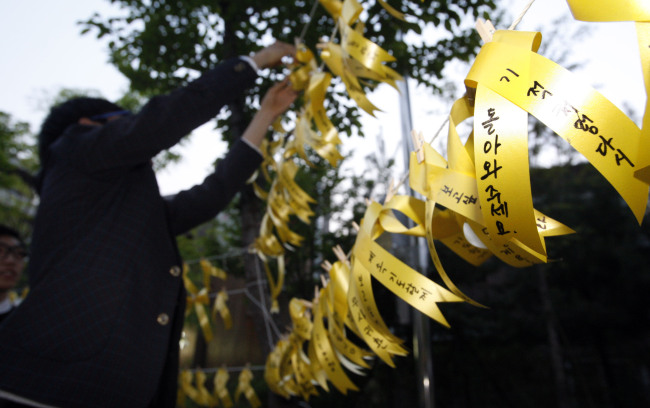 Chuncheon YMCA members in Gangwon Province hang yellow ribbons on trees to honor the dead and wish for the safe return of the missing passengers on board the sunken ferry Sewol on Tuesday. (Yonhap)