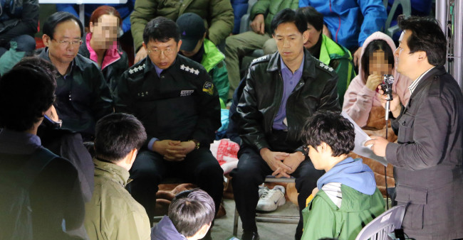 Oceans and Fisheries Minister Lee Ju-young (left) and Coast Guard chief Kim Seok-kyun (second from left) meet with family members of the sunken ferry Sewol's missing passengers at a port on Jindo Island, South Jeolla Province, Thursday. (Yonhap)